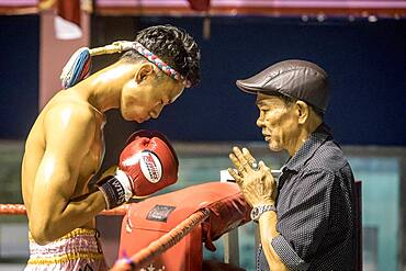 Coach and muay Thai fighter through pre-fight ritual, Bangkok, Thailand