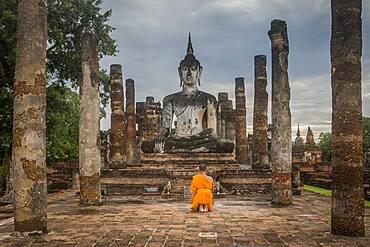 Monk praying, in Wat Mahathat, Sukhothai Historical Park, Sukhothai, Thailand