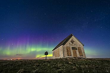 The 1910 Liberty Schoolhouse, a classic pioneer one-room school, on the Alberta prairie under the stars on a spring night, with an aurora dancing to the north. Moonlight provides the illumination. Cassiopeia is above the school. Polaris is at top.