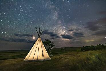 Mars (at left) and the Milky Way (at right) over a single tipi (with another under construction at back) at the Two Trees site at Grasslands National Park, Saskatchewan, August 6, 2018. I placed a low-level warm LED light inside the tipi for the illumination.