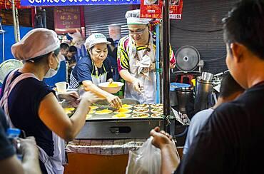 Cooking khanom buang sweet coconut crepes, Street food night market, at Yaowarat road, Chinatown, Bangkok, Thailand