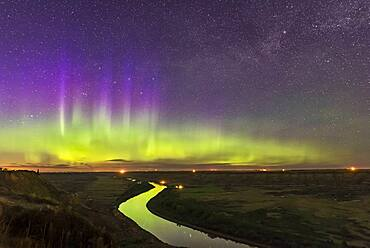 The Northern Lights dance over the sweeping Red Deer River and Badlands of southern Alberta, from Orkney Viewpoint looking north over the valley. The Bleriot Ferry crossing is in the distance at the lights. Cassiopeia is embedded in the purple curtains. The river reflects the aurora light.