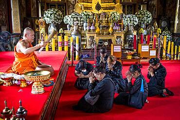 Monk blessing women, in Wat Arun (Temple of Dawn), also called Wat Bangmakok Noek, Bangkok, Thailand
