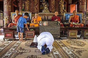 Persons praying, Monks statue, in Wat Phra Singh temple, Chiang Mai, Thailand