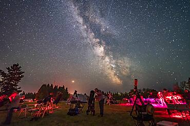 An observer gazes skyward with his Dobsonian reflector telescope at the Saskatchewan Summer Star Party on August 9, 2018, in the Cypress Hills of southwest Saskatchewan, at the Cypress Hills Interprovincial Park, a Dark Sky Preserve. The Milky Way shines to the south. Smoke in the sky obscures the horizon somewhat.