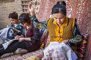 Craftswomen making embroideries, workshop in Yoqubboy Hoja medressa, Khiva, Uzbekistan