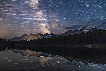 A blend of images to show the stars of the southern sky moving from east to west (left to right) over the peaks of the Continental Divide at Herbert Lake near Lake Louise, in Banff, Alberta. The main peak at left is Mount Temple.