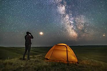 A Park interpreter poses for a scene in Grasslands National Park, Saskatchewan, of stargazing with binoculars under the Milky Way on a dark moonless night. Grasslands is perfect for stargazing as it is a Dark Sky Preserve and the horizon is vast and unobstructed.