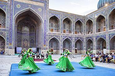 Traditional dance, folklore, in the courtyard of Sher Dor Medressa, Registan, Samarkand, Uzbekistan