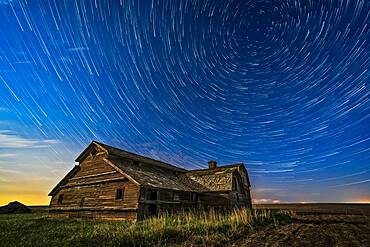 Circumpolar star trails over a grand old barn in southern Alberta, on a fine spring night, May 23, 2018. Illumination is from the waxing gibbous Moon to the south. This is looking north to Polaris at top right. A thunderstorm is on the northern horizon with a lightning bolt as a bonus.