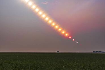 The Sun setting into a pall of forest fire smoke over Alberta from fires in B.C. and elsewhere, on August 17, 2018. This shows the dimming and reddening of the Sun as it set, with it disappearing from view long before it reached the horizon.