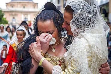 After seeing the Virgin, women in Fallera Costumes crying during Flower offering parade, tribute to `Virgen de los desamparados��, Fallas festival, Plaza de la Virgen square,Valencia