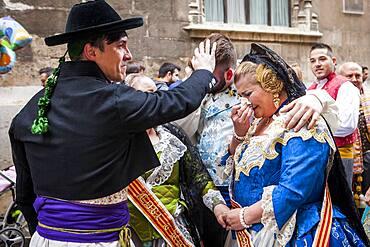 After seeing the Virgin, woman and men in Fallero Costumes crying during Flower offering parade, tribute to `Virgen de los desamparados��, Fallas festival, Plaza de la Virgen square,Valencia