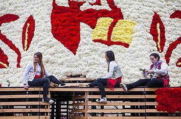 Women placing flower offerings on large wooden replica statue of Virgen de los Desamparados, Fallas festival,Plaza de la Virgen square,Valencia