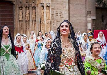 woman looks with emotion the Virgin during flower offering parade,People with Floral tributes to `Virgen de los desamparados��, Fallas festival, Plaza de la Virgen square,Valencia
