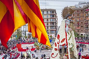 Men placing flower offerings on large wooden replica statue of Virgen de los Desamparados, Fallas festival,Plaza de la Virgen square,Valencia