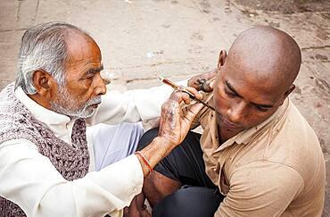 Barber shaving the head and beard of a pilgrim, Dashashwamedh ghat (main ghat), in Ganges river, Varanasi, Uttar Pradesh, India.