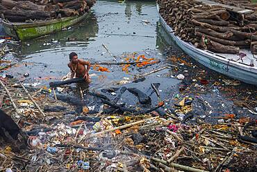 Person who recovers wood used in cremation, which has not burned completely, in Manikarnika Ghat, the burning ghat, on the banks of Ganges river, Varanasi, Uttar Pradesh, India.