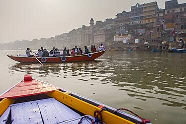 Pilgrims in a boat sailing and praying, Ganges river, in background the ghats, Varanasi, Uttar Pradesh, India.
