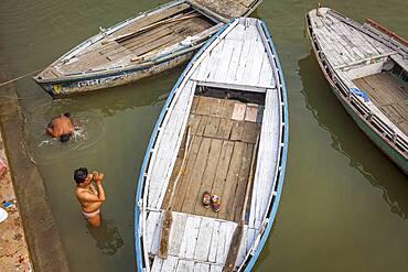 Men praying and bathing, in the ghats of Ganges river, Varanasi, Uttar Pradesh, India.
