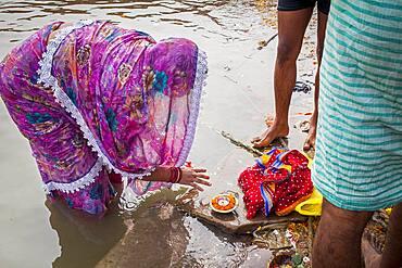 Woman making offering, in the ghats of Ganges river, Varanasi, Uttar Pradesh, India.