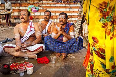 Pilgrims making a ritual offering, and praying, ghats in Ganges river, Varanasi, Uttar Pradesh, India.