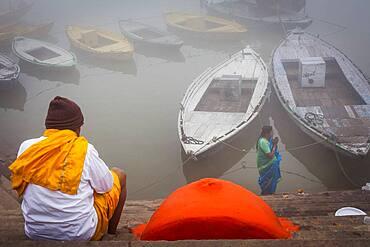 Pilgrims praying, in the ghats of Ganges river, Varanasi, Uttar Pradesh, India.