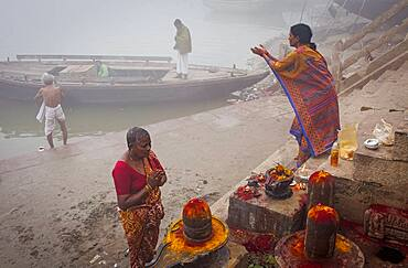 Pilgrims making a ritual offering and praying, ghats of Ganges river, Varanasi, Uttar Pradesh, India.