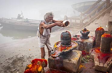 Pilgrim making a ritual offering and praying, ghats of Ganges river, Varanasi, Uttar Pradesh, India.