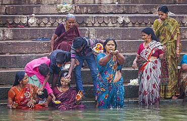 Pilgrims praying and bathing, in the ghats of Ganges river, Varanasi, Uttar Pradesh, India.