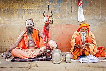 Sadhus praying and begging, in the ghats of Ganges river, Varanasi, Uttar Pradesh, India.