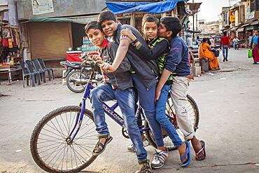 Friends riding a bike, in Raman Reti Road, Historical Center,Vrindavan, Mathura, Uttar Pradesh, India