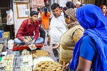 Man selling sweets. Candy store or confectionery, in Gotam Nagar street (main street),Historical Center,Vrindavan, Mathura, Uttar Pradesh, India