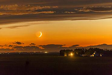 The waxing crescent Moon setting over a nearby farm, on June 26, 2017. Shot at the start of a time-lapse sequence, and shot in haste from home as the Moon appeared from beneath an otherwise very cloudy sky. The dark side of the Moon is lit by Earthshine, prominent despite the Moon's low altitude and bright twilight sky.
