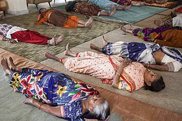 Widows practising Yoga, in Ma Dham ashram for Widows of the NGO Guild for Service, the NGO proposes at widows to wear colorful clothes,  Vrindavan, Mathura district, India