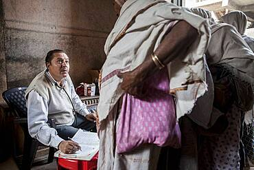 Dr.Ghopal;  Doctor of NGO SOS Woman examining widows, Vrindavan, Mathura district, India