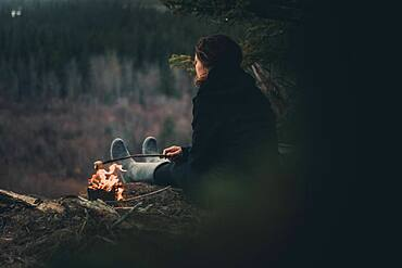 Woman roasting a marshmallow while camping along the edge of a cliff. Yukon Territory, Canada