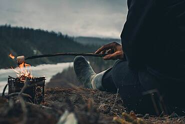 Woman roasting a marshmallow on a cold day early in the year. Yukon Territory, Canada
