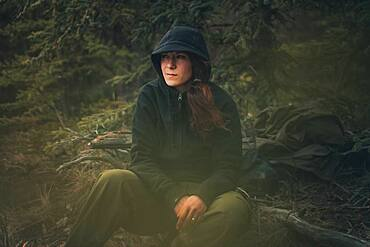 A thirty year old woman sits down and takes a break while hiking through the woods. Yukon Territory, Canada