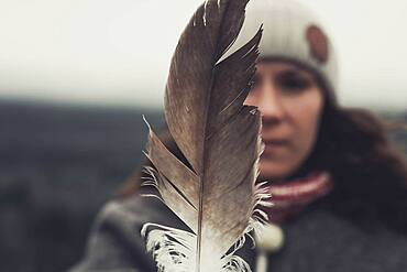 A young Woman shows an eagle's feather. Yukon Territory, Canada