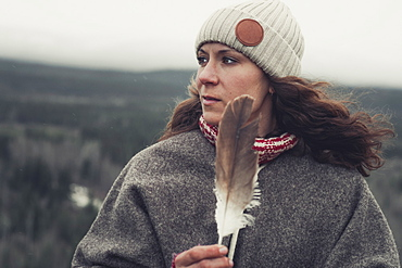 An attractive brunette holds an eagle's feather in her hands and alooks over the land. Yukon Territory, Canada