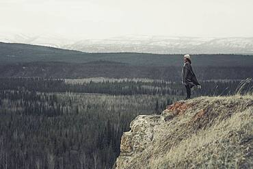 A young Woman is standing at the edge of a cliff with an endless view over forest and mountains. Yukon Territory, Canada
