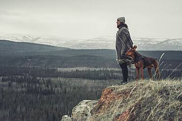 A young Woman is enjoying the view over the land togehter with her dog. Yukon Territory, Canada