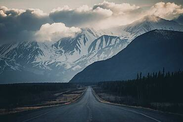 An endless road leads to the mountains, while storm clouds form in the sky. Yukon Territory, Canada