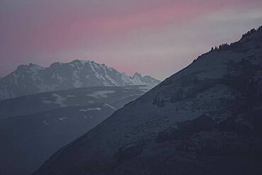 The sky is glowing softly as the sun sets behind the mountains of the Kluane National Park. Yukon Territory, Canada