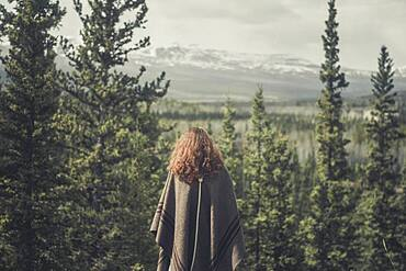 A young woman enjoys the view over forest and mountains. Yukon Territory, Canada