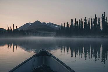 A Canoe glides over the quiet water of a river while the sky starts to glow softly, shortly before the sunrise. Yukon Territory, Canada
