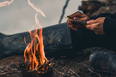 Woman carving a stick to cook over the campfire. Yukon Territory, Canada
