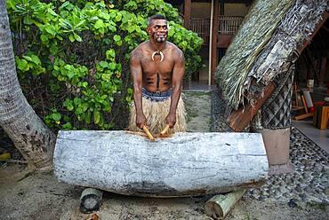 Tradtional Fijian Warrior playing the drum in Malolo Island Resort and Likuliku Resort, Mamanucas island group Fiji