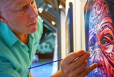 The portrait painter Stephen Bennett doing a polynesian painting in Meridien Hotel on the island of Tahiti, French Polynesia, Tahiti Nui, Society Islands, French Polynesia, South Pacific.